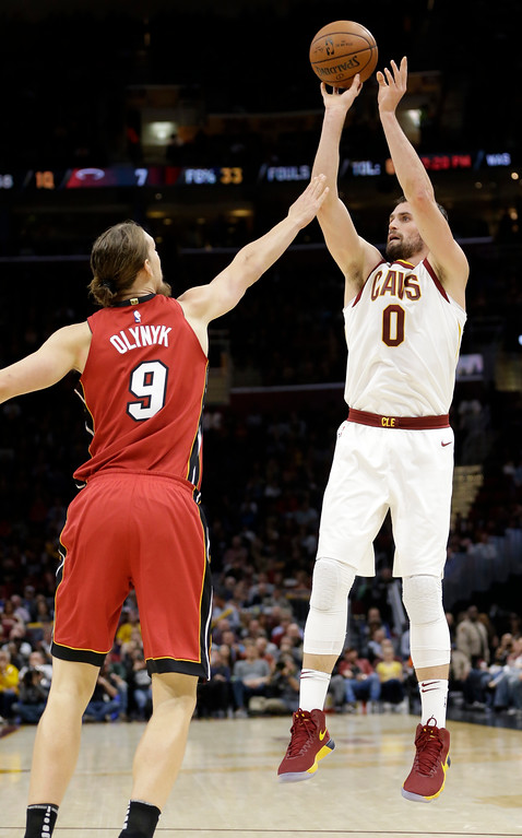 . Cleveland Cavaliers\' Kevin Love (0) shoots over Miami Heat\'s Kelly Olynyk (9) in the first half of an NBA basketball game, Tuesday, Nov. 28, 2017, in Cleveland. (AP Photo/Tony Dejak)