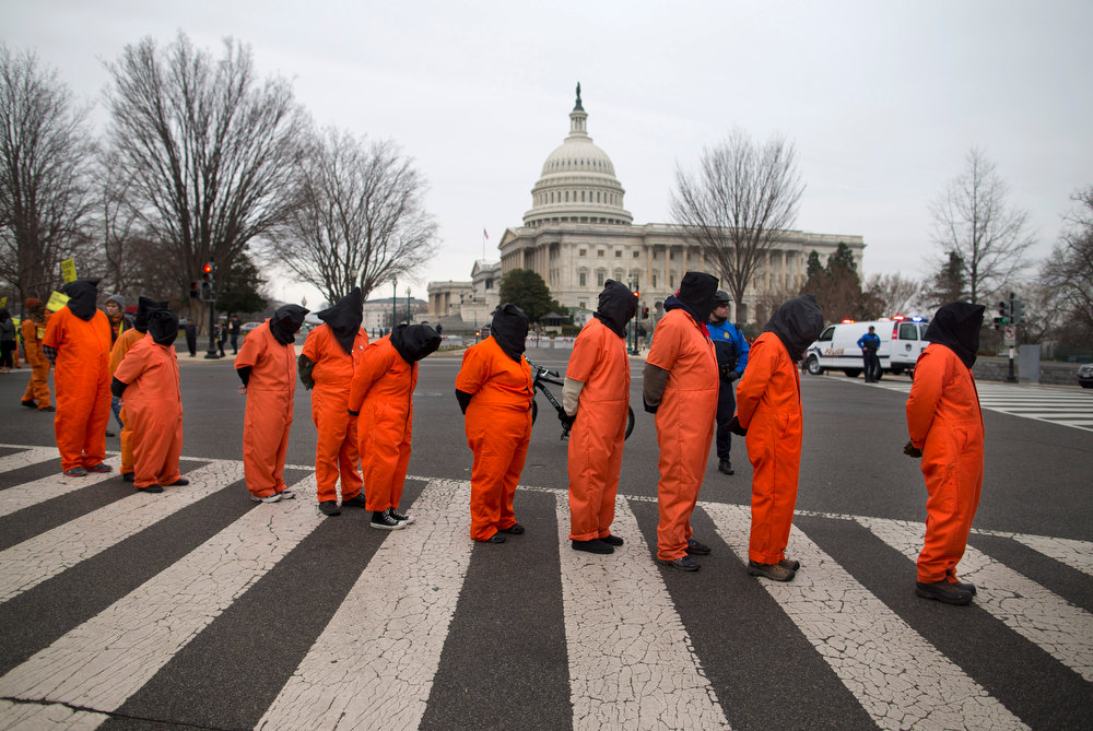 Description of . Demonstrators, dressed as detainees, march past the Capitol building on Capitol Hill in Washington, Friday, Jan. 11, 2013, during a rally against the U.S. military detention facility in Guantanamo Bay, Cuba . The protest marks the 11th anniversary of the first detainees being jailed at Guantanamo Bay. (AP Photo/ Evan Vucci)