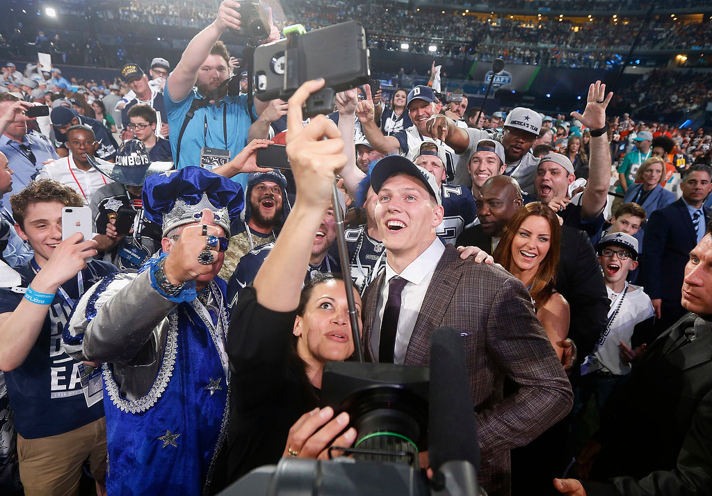 . Boise State\'s Leighton Vander Esch, center right, takes a selfie with Dallas Cowboys fans after being chosen by the team during the first round of the NFL football draft, Thursday, April 26, 2018, in Arlington, Texas. (AP Photo/Michael Ainsworth)