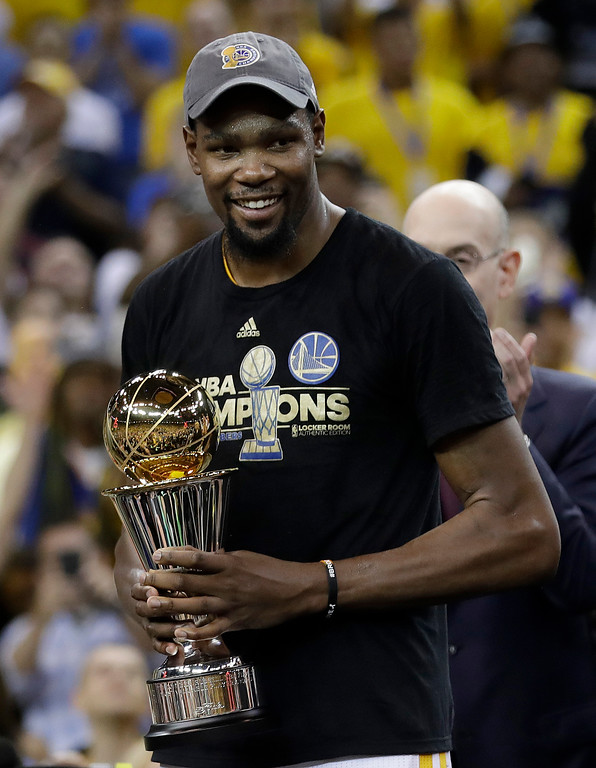 . Golden State Warriors forward Kevin Durant smiles as he holds the Bill Russell NBA Finals Most Valuable Player Award after Game 5 of basketball\'s NBA Finals between the Warriors and the Cleveland Cavaliers in Oakland, Calif., Monday, June 12, 2017. The Warriors won 129-120 to win the NBA championship. (AP Photo/Marcio Jose Sanchez)