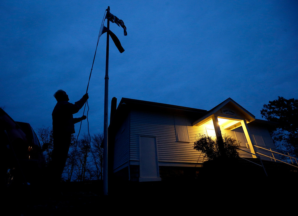 . Bob Wootten raises flags outside the old Brown School as he prepares to open the polling place for voters in the midterm elections Tuesday, Nov. 4, 2014, in rural Wellsville, Kan. (AP Photo/Charlie Riedel)