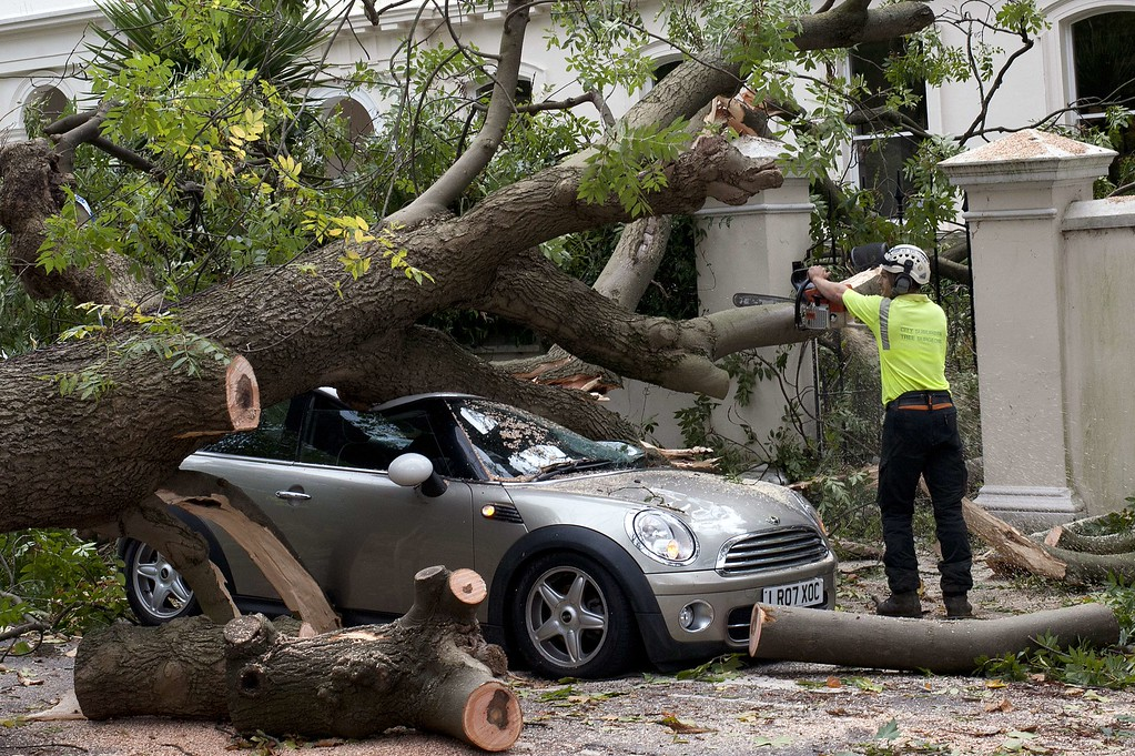 . A contractor works on clearing the debris after a tree fell on car during a storm in London on October 28, 2013.   AFP PHOTO / DANIEL SORABJI/AFP/Getty Images