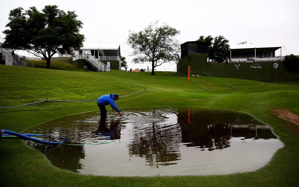 . Grounds crew staff work to remove standing water on the 17th hole after heavy rains delayed Round Two of the AT&T Byron Nelson at the TPC Four Seasons Resort Las Colinas on May 29, 2015 in Irving, Texas.  (Photo by Tom Pennington/Getty Images)