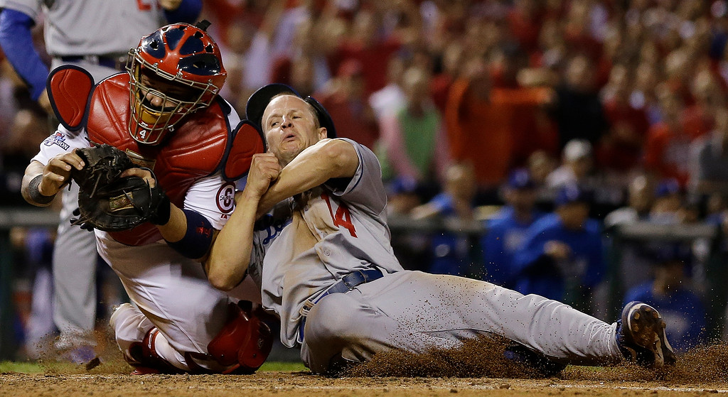 . St. Louis Cardinals catcher Yadier Molina tags out Los Angeles Dodgers\' Mark Ellis at home during the 10th inning of Game 1 of the National League baseball championship series Friday, Oct. 11, 2013, in St. Louis. (AP Photo/Jeff Roberson)