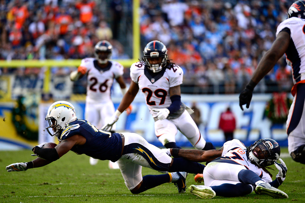 . SAN DIEGO, CA. December 14, - wide receiver Eddie Royal #11 of the San Diego Chargers is stopped by strong safety David Bruton #30 of the Denver Broncos at Qualcomm Stadium December 14, 2014 San Diego, CA (Photo By Joe Amon/The Denver Post)