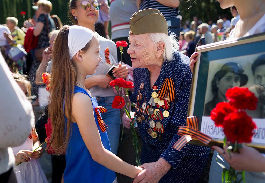 . Olga Vasiljeva, an 93 -year-old veteran of World War II receives flowers at the Antakalnis memorial during Victory Day celebrations in Vilnius, Lithuania, Monday, May 9, 2015. (AP Photo/Mindaugas Kulbis)