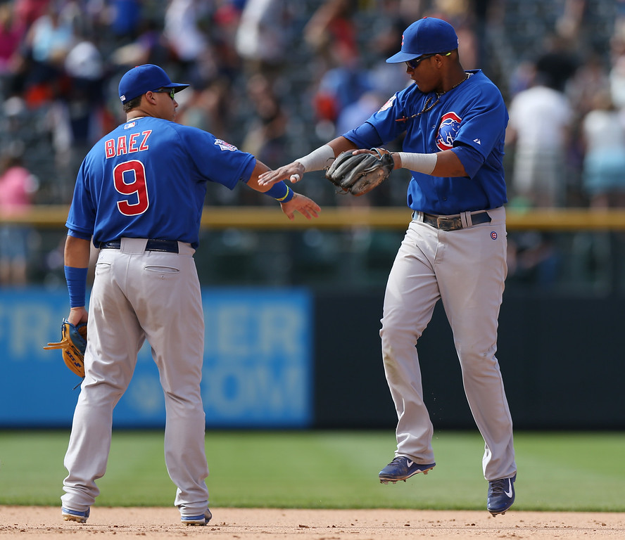 . Chicago Cubs second baseman Javier Baez, left, is congratulated by shortstop Starlin Castro after the Cubs\' 6-2 victory over the Colorado Rockies in a baseball game in Denver on Thursday, Aug. 7, 2014. (AP Photo/David Zalubowski)