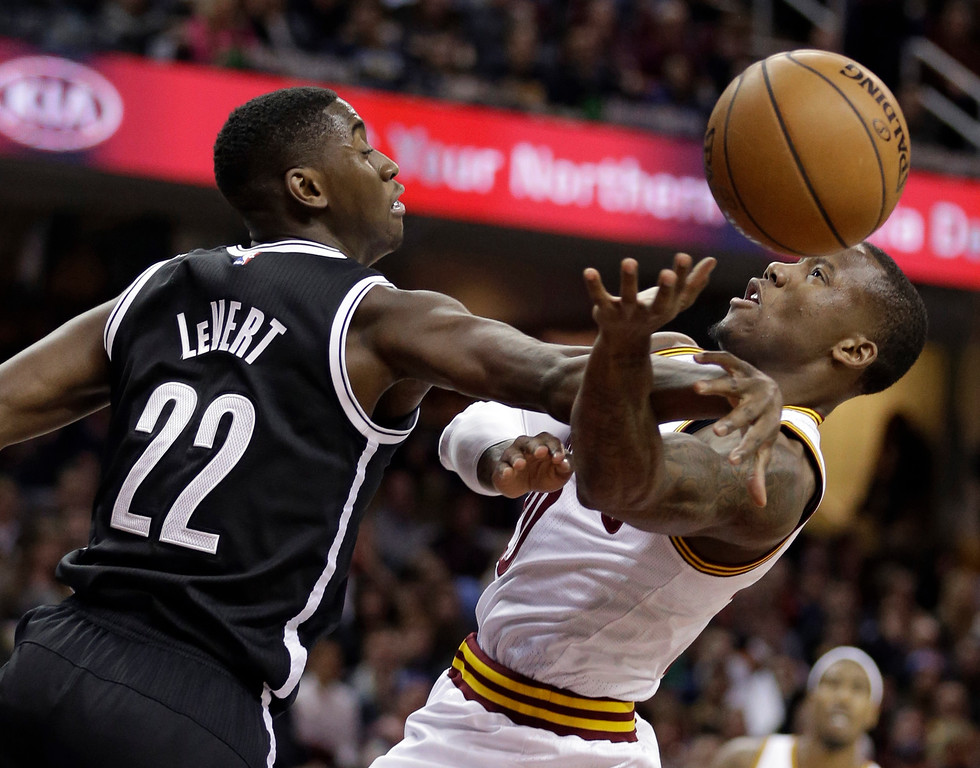 . Brooklyn Nets\' Caris LeVert (22) fouls Cleveland Cavaliers\' Kay Felder (20) in the second half of an NBA basketball game, Friday, Dec. 23, 2016, in Cleveland. (AP Photo/Tony Dejak)