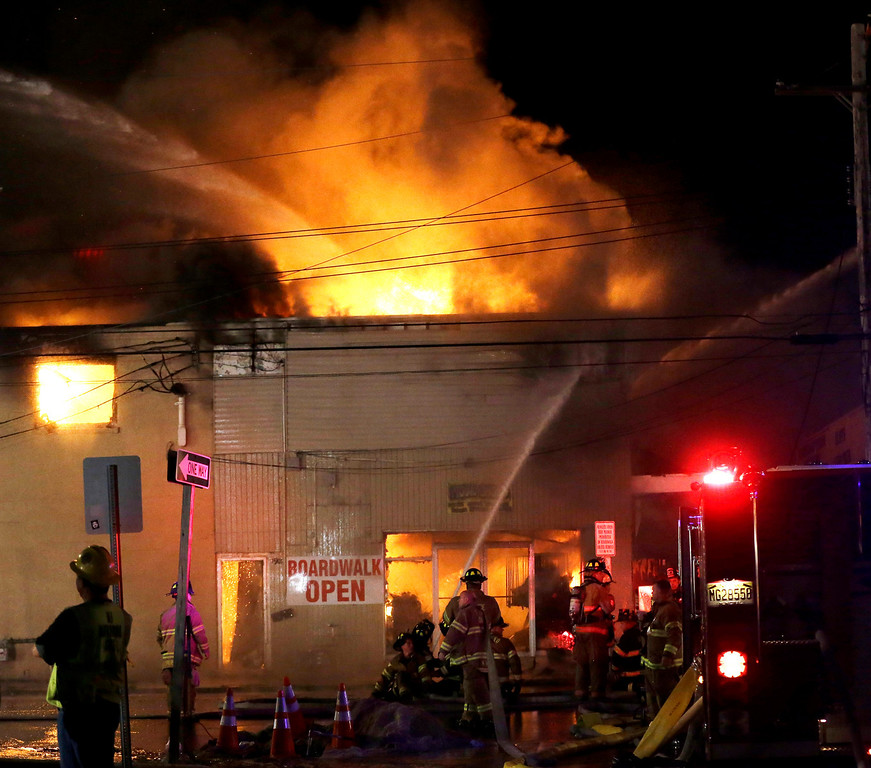 . Firefighters battle a blaze in a building on the Seaside Park boardwalk on Thursday, Sept. 12, 2013, in Seaside Park, N.J. The fire began in a frozen custard stand on the Seaside Park section of the boardwalk and quickly spread north into neighboring Seaside Heights. (AP Photo/Julio Cortez)