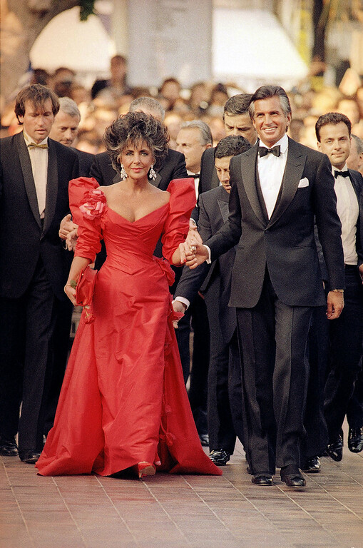 . American movie star Elizabeth Taylor, escorted by George Hamilton arrives at the Cannes Festival Palace in Cannes, France to attend the official gala for the Cannes Film Festival 40th Anniversary as seen in the Wednesday, May 13, 1987 photo. (AP Photo/Michael Lipchutz)