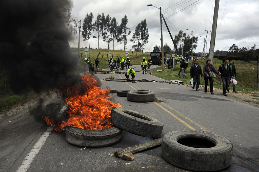 . Colombian police officers clear a road blocked set by farmers demanding government subsidies and greater access to land, in La Calera, Cundinamarca department, on August 23, 2013. A five-day-old farmworkers\' protest in Colombia claimed its first fatality Friday when a man on a motorcycle crashed and died at a roadblock, police said Friday. Since the protests began Monday, farmworkers have closed roads at dozens of points in across the country, blocking the passage of cargo trucks and other vehicles from makeshift camps erected on sides of roads. EITAN ABRAMOVICH/AFP/Getty Images