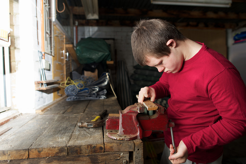 Teenage boy tightening a vice on a piece of wood