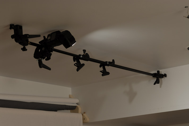 """Photoflex support for 42"""" diffuser adjusted and used as a pole for Hair light made with Nikon SB-800.  The cieling and wall were tapped at 1/4"""" and a spigot was added at each end to received a typical lightstand bracket. A super clamp Manfrotto #035 slides on the bar to hold the SB-800."""