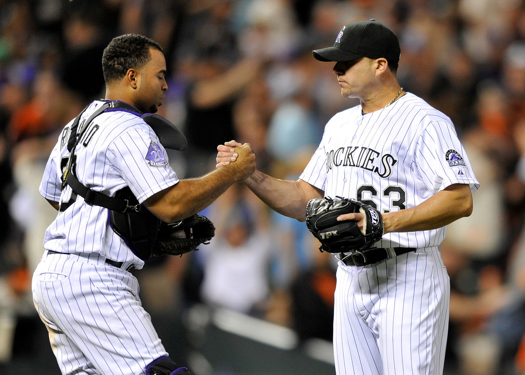 . Colorado Rockies catcher Wilin Rosario (20) celebrates with relief pitcher Rafael Betancourt (63) following a baseball game against the San Francisco Giants  on Friday, May 17, 2013, in Denver. Colorado Defeated San Francisco 10-9. (AP Photo/Jack Dempsey)
