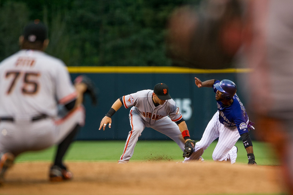 . Marco Scutaro #19 of the San Francisco Giants applies a tag for an out as Dexter Fowler #24 of the Colorado Rockies slides into second base with an attempted steal in the first inning of a game at Coors Field on August 26, 2013 in Denver, Colorado. (Photo by Dustin Bradford/Getty Images)