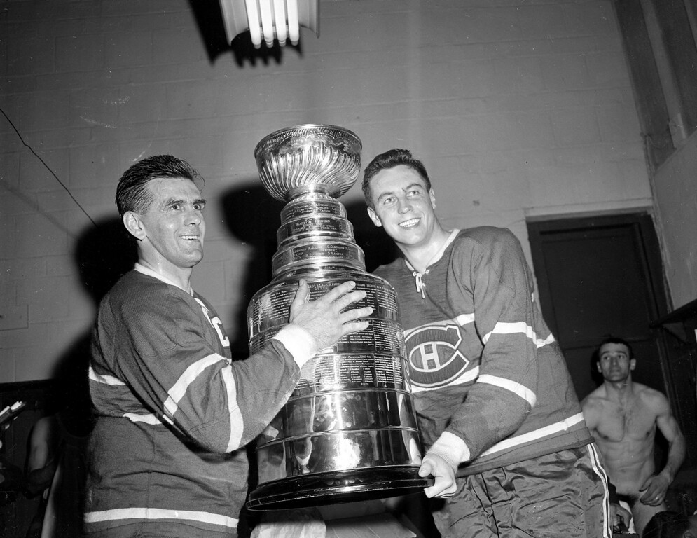 . Maurice Richard (left) and Jean Beliveau, of the Montreal Canadiens smile happily in the dressing room with the Stanley Cup after defeating the Boston Bruins 5-3 at the Boston Garden on April 20, 1958 to win the National Hockey League Championship.  (AP Photo)