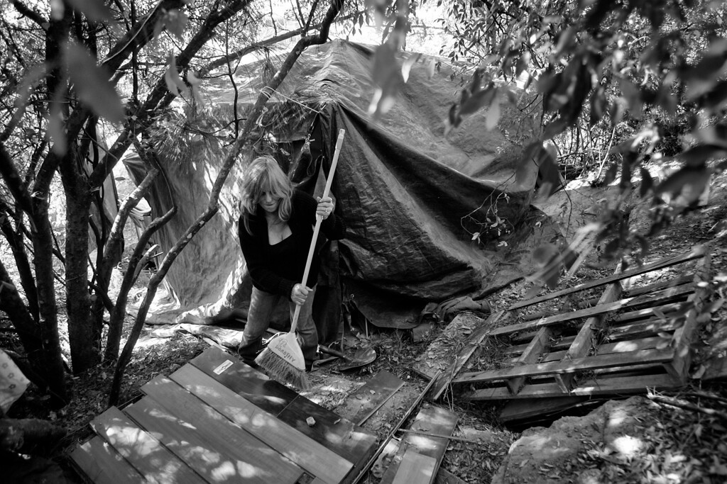 . Dorothy works on creating a shower behind her tent, which is covered by tarps.