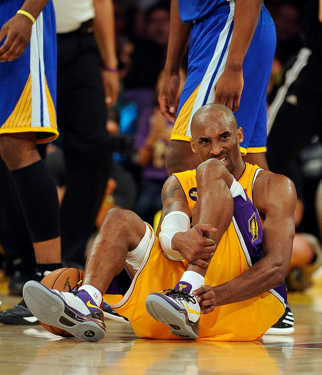 . The Lakers\' Kobe Bryant #24 sits on the court after hurting his ankle during their game against the Warriors at the Staples Center in Los Angeles Friday, April 12, 2013. The Lakers beat the Warriors 118-116. (Hans Gutknecht/Staff Photographer)