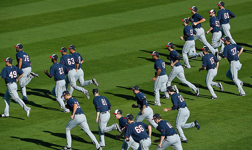 . Twins pitchers and catchers loosen up their leg muscles in 80-degree weather at Hammond Stadium on Thursday. (Pioneer Press: Ben Garvin)