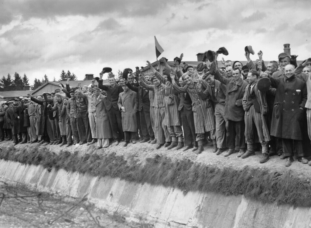 . 7th May 1945:  Liberated prisoners from Dachau, the German concentration camp wave in joy. Those wearing striped uniforms are political prisoners whose fate was cremation if they had not been liberated by the US 7th Army.  (Photo by Horace Abrahams/Keystone/Getty Images)