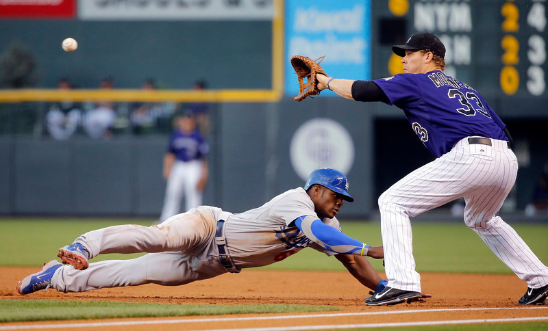 . Los Angeles Dodgers\' Yasiel Puig dives back to first as the ball comes to Colorado Rockies first baseman Justin Morneau (33) during the first inning of a baseball game Monday, Sept. 15, 2014, in Denver. (AP Photo/Jack Dempsey)