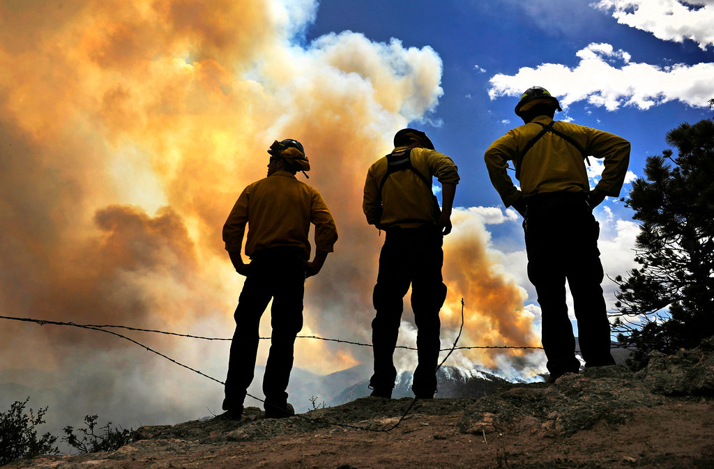 . A fire crew, from left, Tiras Roach, Jeff Wegert and Mark Schmidt, watch as the High Park Fire grows, Wednesday, June 13, 2012, near Glacier View Meadows during an expanded evacuation order for the area.
