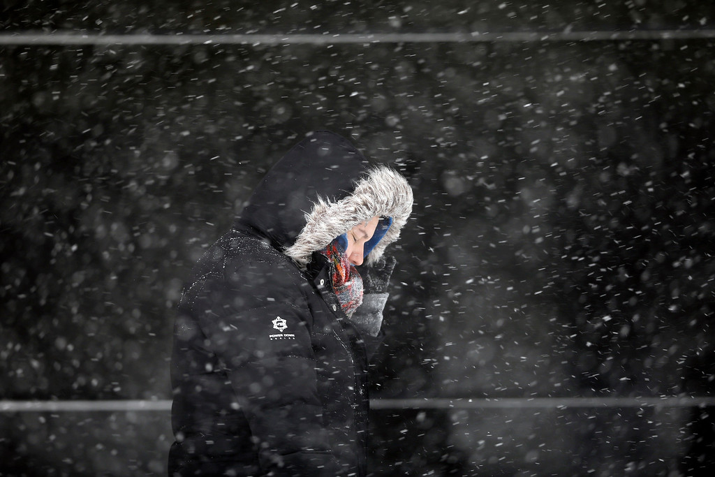 . A woman walks along Broad Street through a snowstorm, Saturday, Jan. 23, 2016, in Philadelphia. (AP Photo/Matt Slocum)