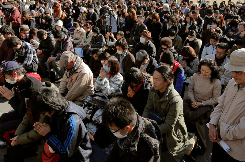 . People observe a moment of silence for the victims of the March 11, 2011 earthquake and tsunami during an event at a park  in Tokyo, Monday, March 11, 2013.  (AP Photo/Itsuo Inouye)