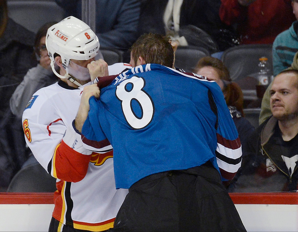 . Jan Hejda (8) of the Colorado Avalanche grabs ahold of Cory Sarich (6) of the Calgary Flames by the face mask as they fight along the boards in the first period April 8, 2013 at Pepsi Center. (Photo By John Leyba/The Denver Post)