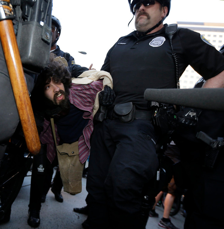 . A protester who was arrested during a May Day march that began as an anti-capitalism protest and turned into demonstrators clashing with police is carried away by police Wednesday, May 1, 2013, in downtown Seattle. (AP Photo/Ted S. Warren)
