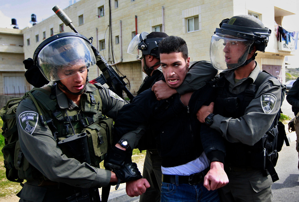 . Isreali border policemen arrest a Palestinian man during a protest to support Palestinian prisoners, outside Ofer, an Israeli military prison near the West Bank city of Ramallah, Thursday, Feb. 28, 2013. (AP Photo/Majdi Mohammed)