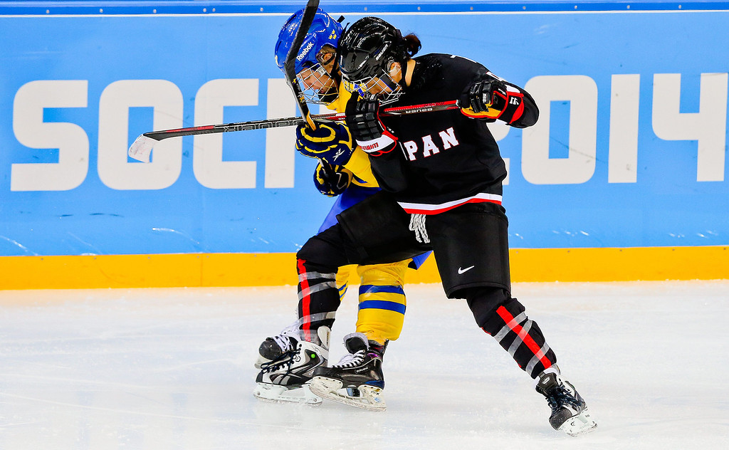 . Mika Hori (R) of Japan fights for the pack with Pernilla Winberg (L) of Sweden during the match between Sweden and Japan at the Shayba Arena in the Ice Hockey tournament at the Sochi 2014 Olympic Games, Sochi, Russia, 09 February 2014.  EPA/SRDJAN SUKI
