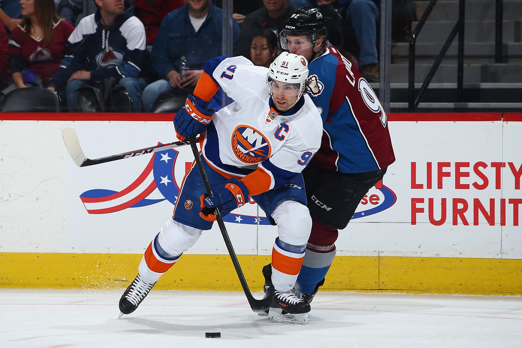 . DENVER, CO - JANUARY 10:  John Tavares #91 of the New York Islanders controls the puck as Gabriel Landeskog #92 of the Colorado Avalanche is draws a penalty for hooking in the first period at Pepsi Center on January 10, 2014 in Denver, Colorado.  (Photo by Doug Pensinger/Getty Images)