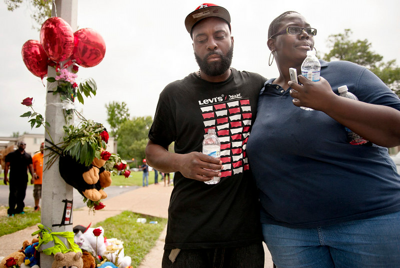 . Mourners embrace at a spontaneous memorial for shooting victim Michael Brown, 18, Sunday, Aug. 10, 2014 at the scene of the shooting in Ferguson, Mo. Brown, who was killed in a confrontation with police in the St. Louis suburb, was shot Saturday, Aug. 9, 2014. Brown died following a confrontation with police, according to St. Louis County Police Chief Jon Belmar, who spoke at a news conference Sunday. (AP Photo/Sid Hastings)