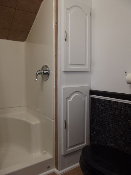 The bath in the third floor studio contains a two-person shower, black commode, and a small linen closet.
