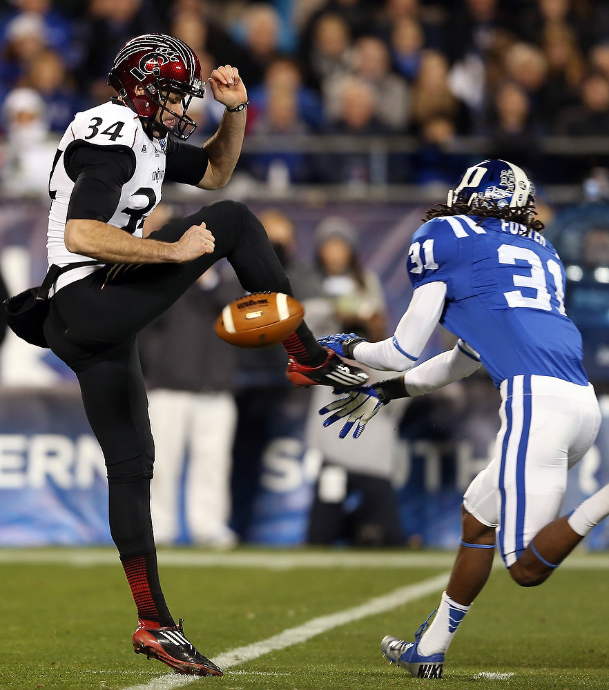 Description of . Pat O'Donnell #34 of the Cincinnati Bearcats has his punt blocked by Tony Foster #31 of the Duke Blue Devils during their game at Bank of America Stadium on December 27, 2012 in Charlotte, North Carolina.  (Photo by Streeter Lecka/Getty Images)