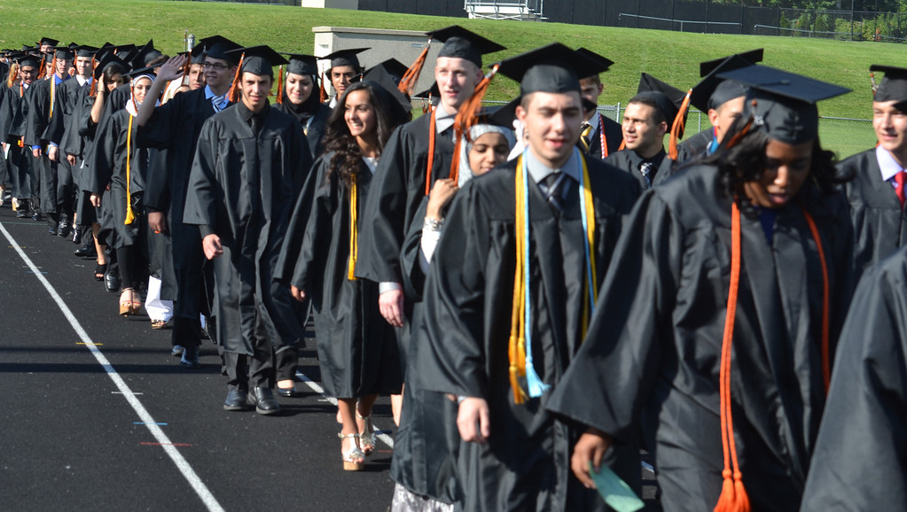 . Dearborn High School students walk along the track to the bleachers on the field at the start of the ceremony. (Photo by Joe Slezak)