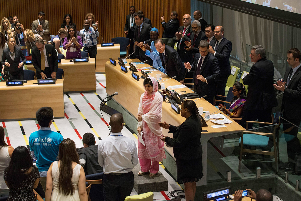 ". NEW YORK, NY - JULY 12:  Malala Yousafzai, the 16-year-old Pakistani advocate for girls education who was shot in the head by the Taliban, is given a standing ovation after speaking at the United Nations (UN) Youth Assembly on July 12, 2013 in New York City. The United Nations declared July 12, ""Malala Day.\"" Yousafzai also celebrates her birthday today.  (Photo by Andrew Burton/Getty Images)"