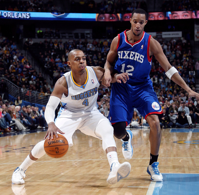 . Denver Nuggets guard Randy Foye, left, works the ball inside for a shot as Philadelphia 76ers forward Evan Turner covers in the third quarter of the Sixers\' 114-102 victory in an NBA basketball game in Denver on Wednesday, Jan. 1, 2014. (AP Photo/David Zalubowski)