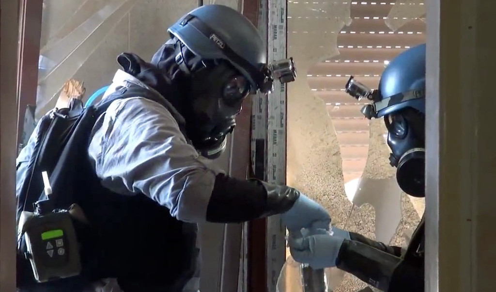 . In this file image taken from video obtained from the Shaam News Network Thursday, Aug. 29, 2013, which has been authenticated based on its contents and other AP reporting, members of a chemical weapons investigation team take samples from the ground in the Damascus countryside of Zamalka, Syria. The Organization for the Prohibition of Chemical Weapons won the Nobel Peace Prize on Friday, Oct. 11, 2013, for working to eliminate the scourge that has haunted generations from World War I to the battlefields of Syria. (AP Photo/Shaam News Network via AP video, File)