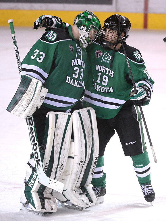 . DENVER, CO. - JANUARY 24:  North Dakota center Rocco Grimaldi (19) congratulated goalie Clarke Saunders on the win. The University North Dakota out hustled the Pioneers to a 4-2 win Friday night, January 24, 2014. Photo By Karl Gehring/The Denver Post