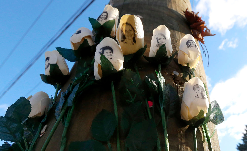 Description of . Roses with photos of shooting victims are posted on a light post at a makeshift memorial near the main intersection of the Sandy Hook village of Newtown, Conn., as the town continues to cope in the aftermath of the Sandy Hook Elementary School shooting, Wednesday, Dec. 19, 2012. The gunman, Adam Lanza, walked into Sandy Hook Elementary School in Newtown,  Dec. 14, and opened fire, killing 26 people, including 20 children, before killing himself. (AP Photo/Julio Cortez)