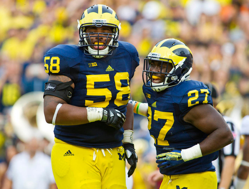 . Michigan offensive lineman Chris Bryant and running back Derrick Green (27) celebrate a touchdown by Green in the third quarter. (AP Photo/Tony Ding)