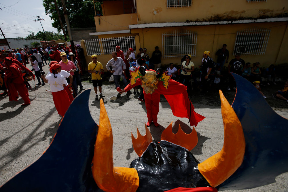 . People dressed as a dancing devils perform on the streets in San Francisco de Yare, Venezuela, Thursday, May 30, 2013. The descendants of African slaves donned colorful masks and bright red costumes as they danced through the streets of this small Venezuelan town on Thursday for its annual commemoration of Corpus Christi, a Roman Catholic holiday celebrating the transformation of the body and blood of Christ into bread and wine. (AP Photo/Fernando Llano)
