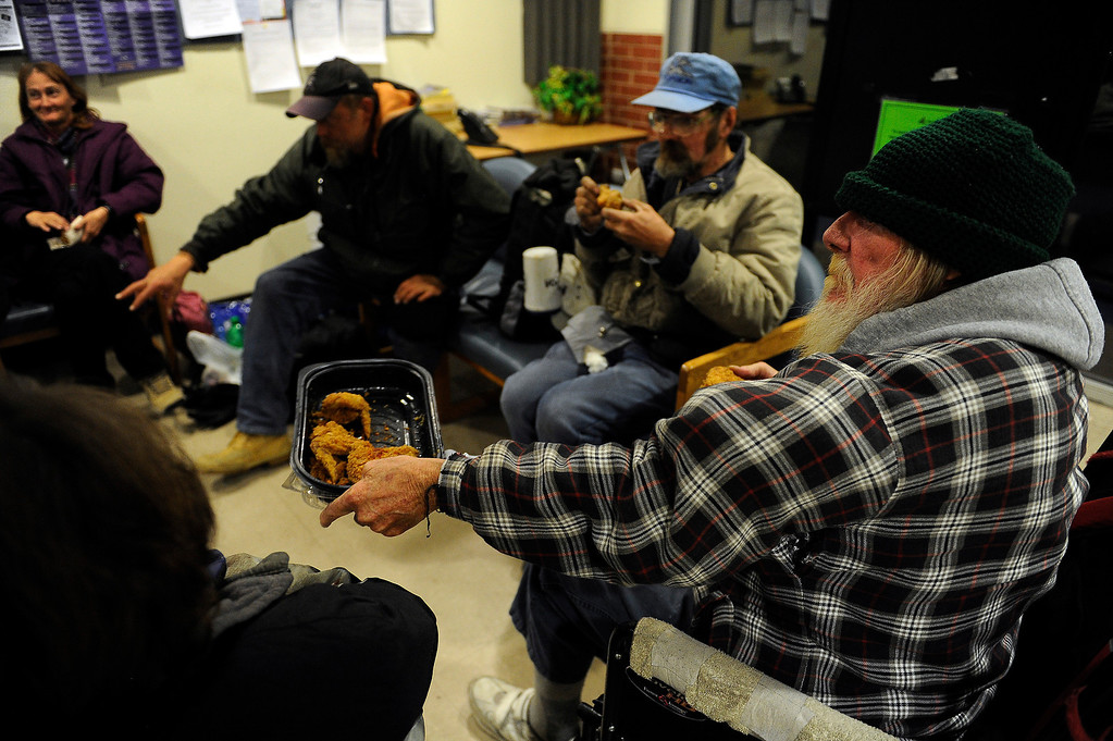. WESTMINSTER, CO - JANUARY 22: Moon, no last name, passes a tray of chicken around as he and other homeless people  wait for a bus in the lobby of the Jefferson County Action Center in Lakewood, Colorado to transport them to a local church to stay the night on January 22, 2014. The Jefferson County Action Center began partnering with churches last year to offer emergency shelter for the homeless on severe weather nights. (Photo by Seth McConnell/The Denver Post)
