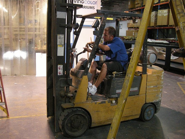 . John drives the forklift, eager to transport the fabled Aquaway tank. The biggest private aquarium in South Florida is 4,500 gallons and weighs over forty thousand pounds and now the client, Fabio wants the guys to top that. (Photograph provided by Sharp Entertainment)