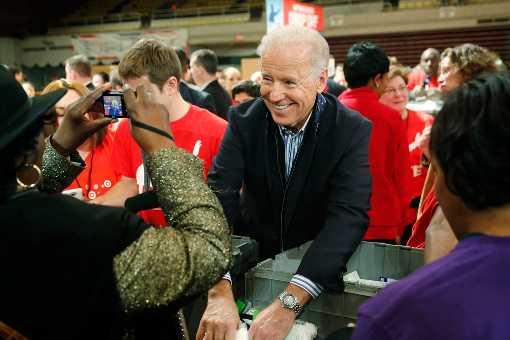 Description of . A volunteer stops to photograph U.S. Vice President Joe Biden as he helps assemble care kits for U.S. military service members and veterans at a Unite America in Service event at the National Guard Armory in Washington, January 19, 2013. Biden and his family volunteered for the event during the National Day of Service as part of the 57th Presidential Inauguration. REUTERS/Jonathan Ernst