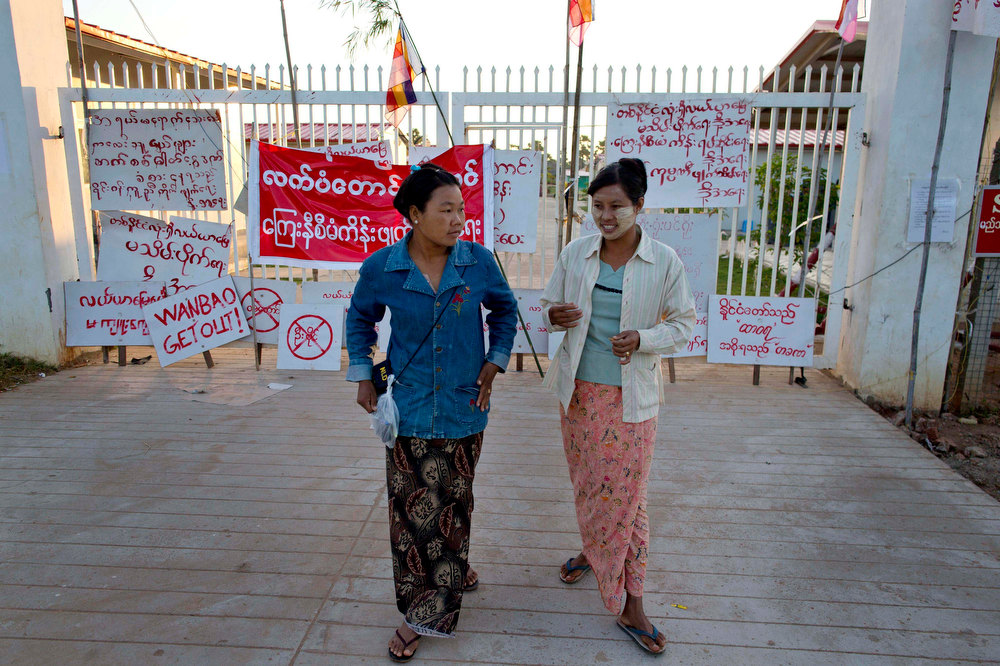 Description of . Activists Thwe Thwe Win, left, and Aye Net walk after re-arranging placards placed at the entrance to Chinese mine company Wan Bao Co. Ltd. facilities in Letpadaung mine, Monywa township, northwestern Myanmar, Wednesday, Nov. 28, 2012. Hundreds of Buddhist monks and villagers occupying the mine, they said is causing environmental, social and health problems, defied a government order to leave by Wednesday, saying they will stay until the project is halted. (AP Photo/Gemunu Amarasinghe)