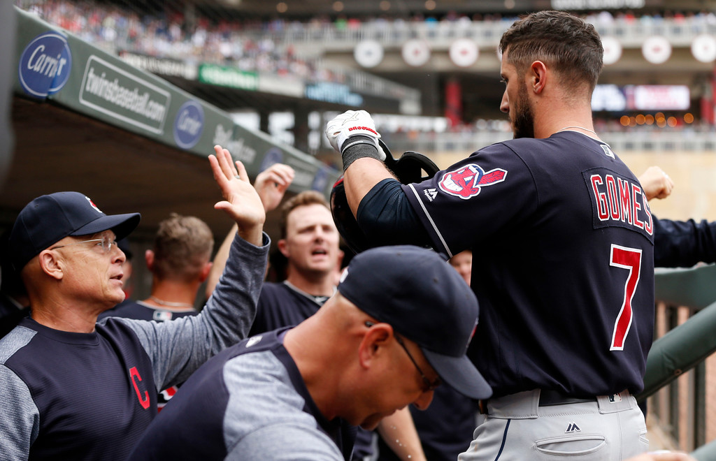 . Cleveland Indians\' Yan Gomes,, right, is congratulated in the dugout after his three-run home run off Minnesota Twins relief pitcher Ryan Pressly in the eighth inning of the first game of a baseball doubleheader Thursday, Aug. 17, 2017, in Minneapolis. The Indians won 9-3. (AP Photo/Jim Mone)