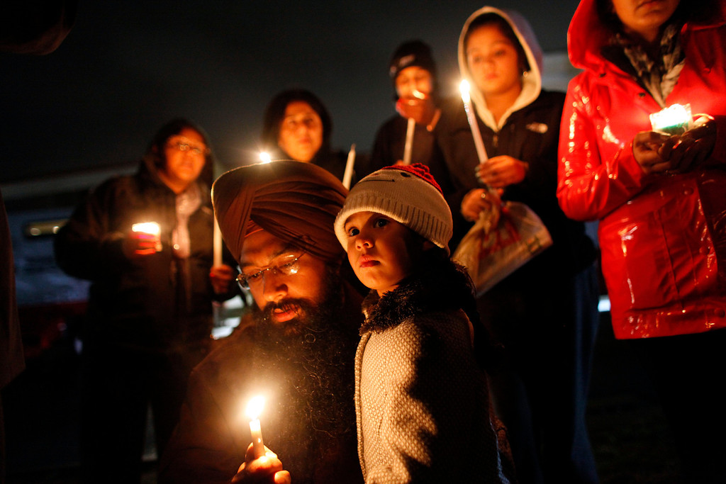 . Eknoor Kaur, 3, stands with her father Guramril Singh during a candlelight vigil outside Newtown High School before an interfaith vigil with President Barack Obama, Sunday, Dec. 16, 2012, in Newtown, Conn.  A gunman walked into Sandy Hook Elementary School in Newtown Friday and opened fire, killing 26 people, including 20 children. (AP Photo/Jason DeCrow)